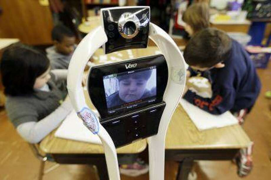 In this Thursday, Jan. 24, 2013 photo, Devon Carrow attends Winchester Elementary School from home while operating a robot in the classroom, in West Seneca N.Y. Carrow's life-threatening allergies don't allow him to go to school. But the 4-foot-tall robot with a wireless video hookup gives him the school experience remotely, allowing him to participate in class, stroll through the hallways, hang out at recess and even take to the auditorium stage when there's a show. (AP Photo/David Duprey) Photo: ASSOCIATED PRESS / AP2013