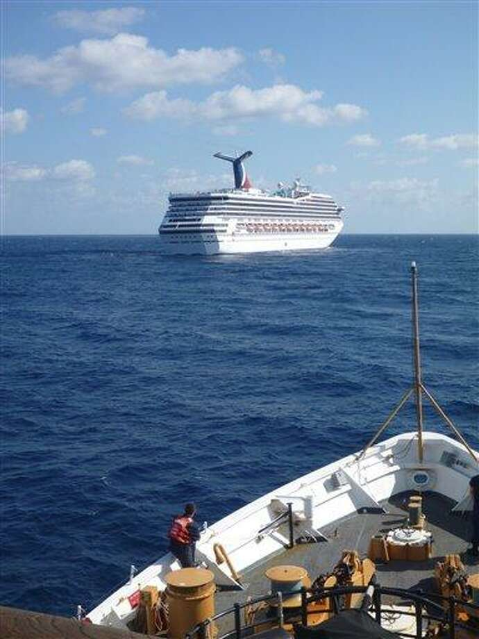In this image released by the U.S. Coast Guard on Feb. 11, 2013, the Coast Guard Cutter Vigorous patrols near the cruise ship Carnival Triumph in the Gulf of Mexico, Feb. 11, 2013. The Carnival Triumph has been floating aimlessly about 150 miles off the Yucatan Peninsula since a fire erupted in the aft engine room early Sunday, knocking out the ship's propulsion system. No one was injured and the fire was extinguished. AP Photo/U.S. Coast Guard- Lt. Cmdr. Paul McConnell Photo: AP / US Coast Guard