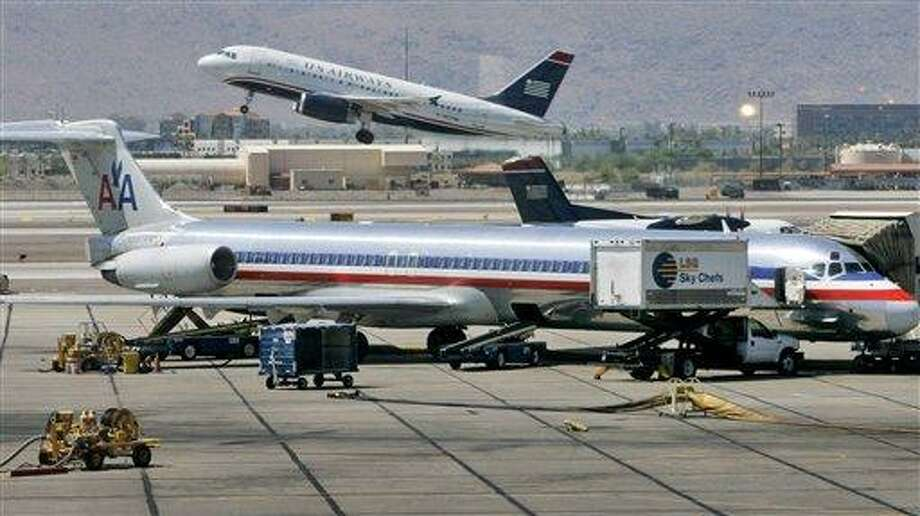 FILE - In this June 23, 2008 file photo, a US Airways jet takes off as an American Airlines jet is prepped for takeoff at Sky Harbor International Airport in Phoenix. The merger of US Airways and American Airlines has given birth to a mega airline with more passengers than any other in the world. (AP Photo/Matt York, File) Photo: AP / AP