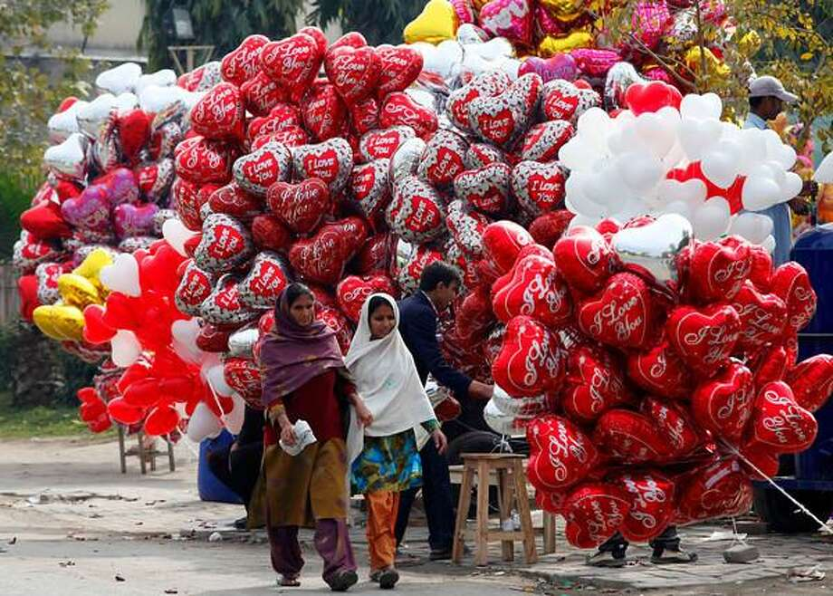 Women walk past heart-shaped balloons on Valentine's Day in Lahore, February 14, 2013. REUTERS/Mohsin Raza