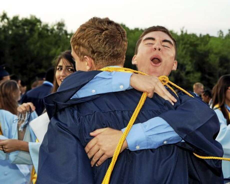 Sandy Aldieri/Special to the Press/Drew Cietek hugs friend, Chris Polson, while fellow classmate Fatima Bishtawi looks on as graduates celebrated after the Middletown High graduation ceremonies on Friday.