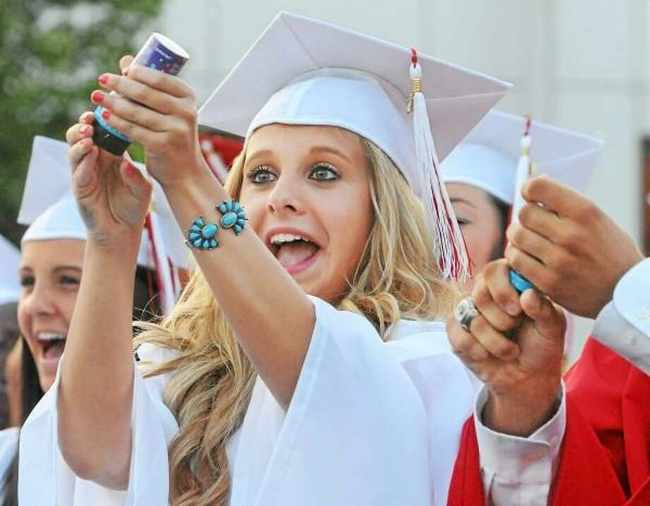 Catherine Avalone/The Middletown Press Haley Kobos works out releasing the confetti as her classmates from class of 2013 at Cromwell High School graduation celebrate Friday evening. / TheMiddletownPress