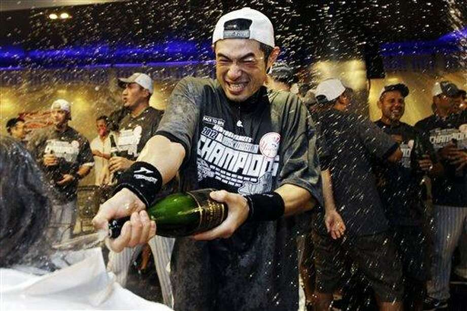 New York Yankees' Ichiro Suzuki douses the team photographer as teammates celebrate in the clubhouse after their 14-2 win over the Boston Red Sox in a baseball game and clinched the American League East title at Yankee Stadium in New York, Wednesday, Oct. 3, 2012. (AP Photo/Kathy Willens) Photo: AP / AP