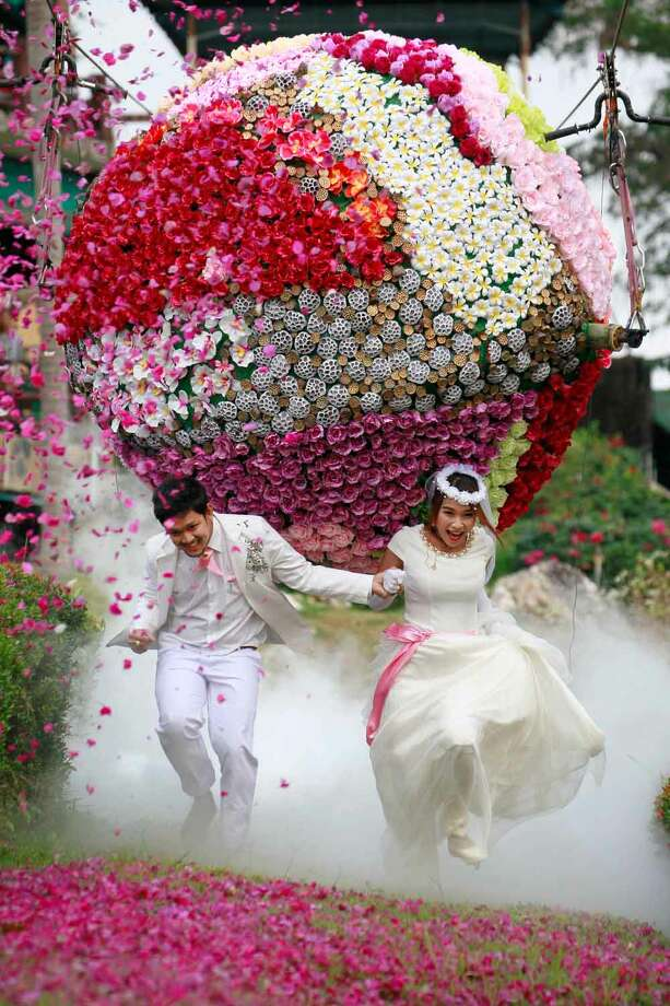Prasit Rangsitwong, left, and Varutton Rangsitwong run away from a giant flower ball as a part of an adventure-themed wedding ceremony in Prachinburi province, Thailand, Wednesday, Feb. 13, 2013, on the eve of Valentine's Day. (AP Photo/Wason Wanichakorn) Photo: ASSOCIATED PRESS / AP2013