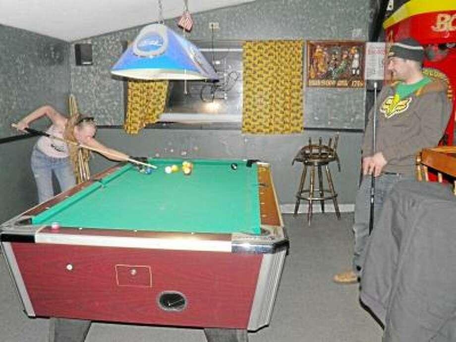 Matt Bartholomew watches while his girlfriend, Jennifer Higgins, cues up at the Hitchin' Post Tavern in Durham.