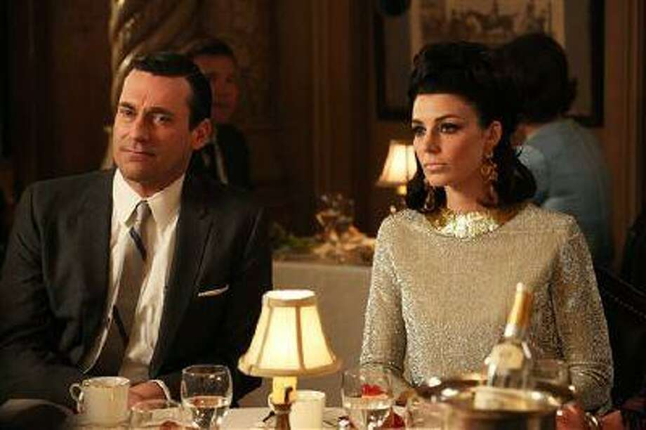 "This TV publicity image released by AMC shows Jon Hamm as Don Draper, left, and Jessica Pare as Megan Draper in a scene from ""Mad Men."" The season finale airs Sunday, June 23, on AMC. (AP Photo/AMC, Michael Yarish) Photo: AP / AMC"