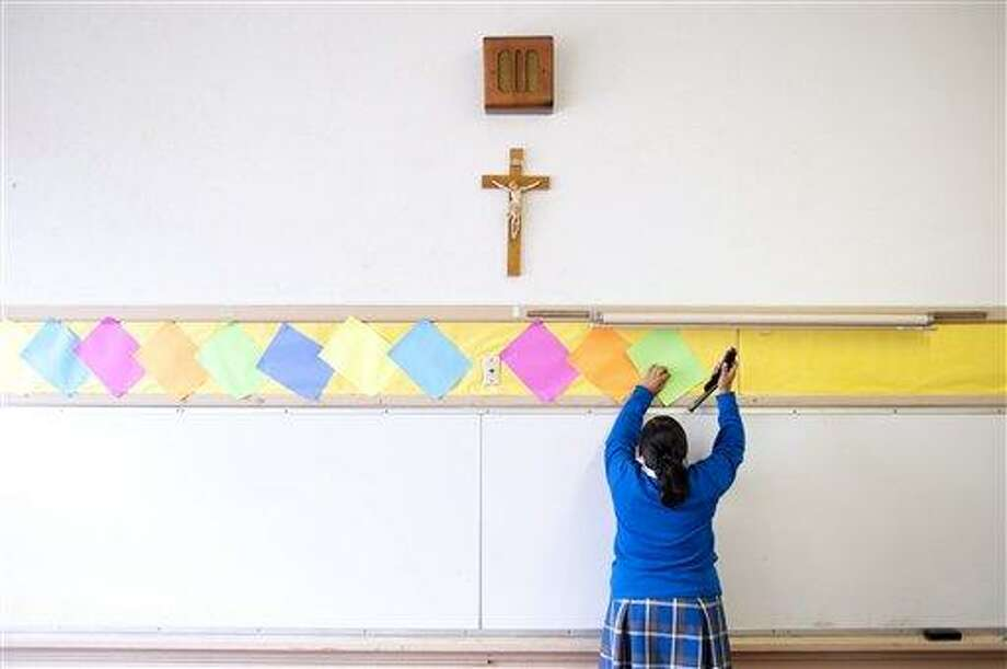 This July 18, 2012, photo shows Adriana Landeros stapling colored paper to the wall of a classroom after summer school at Our Lady of Lourdes in Los Angeles. Many students, such as Landeros, volunteer their time after class to help improve the school in hopes of building enrollment. (AP Photo/Grant Hindsley) Photo: AP / AP