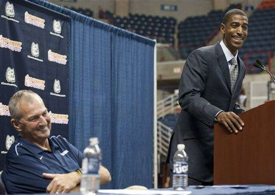 New Connecticut head coach Kevin Ollie, right, smiles as retired coach Jim Calhoun looks on during a news conference announcing Calhoun's retirement, Thursday, Sept. 13, 2012,  in Storrs, Conn.  Ollie, an assistant coach under Calhoun, will succeed him.  (AP Photo/Jessica Hill) Photo: AP / FR125654 AP