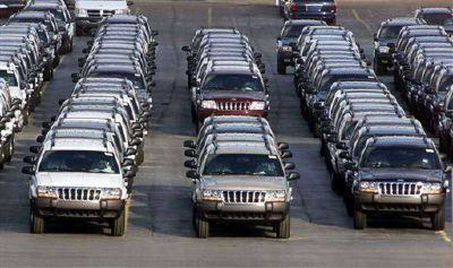 FILE - In this file photo taken Fed. 2, 2001, rows of 2001 Jeep Grand Cherokees are lined up outside the Jefferson North Assembly Plant in Detroit. Chrysler is refusing a request by U.S. safety regulators to recall about 2.7 million vehicles to fix fuel tanks that could leak and cause fires in rear-end collisions.The company says it's been asked by the government to recall Jeep Grand Cherokees from 1993 through 2004 and Jeep Libertys from 2002 through 2007. But Chrysler says in a statement that the SUVs are safe and not defective. (AP Photo/Carlos Osorio, File) Photo: AP / AP