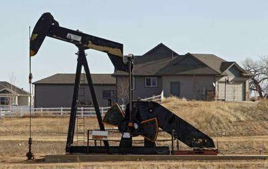 This photo taken on Thursday, Jan. 19, 2012, near Frederick, Colo., shows an oil pump jack working on a property across from a subdivision. (AP Photo/Ed Andrieski) Photo: AP / AP