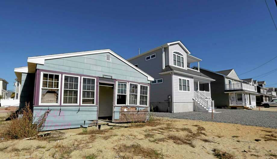 This Friday, Oct. 18, 2013 photo shows the vacation home of Cora Hoch, left, in Lavallette, N.J. The home, which was damaged by Superstorm Sandy, has been gutted and no repairs have been made to it while neighbor homes are up and running again. Photo: Julio Cortez — The Associated Press  / AP