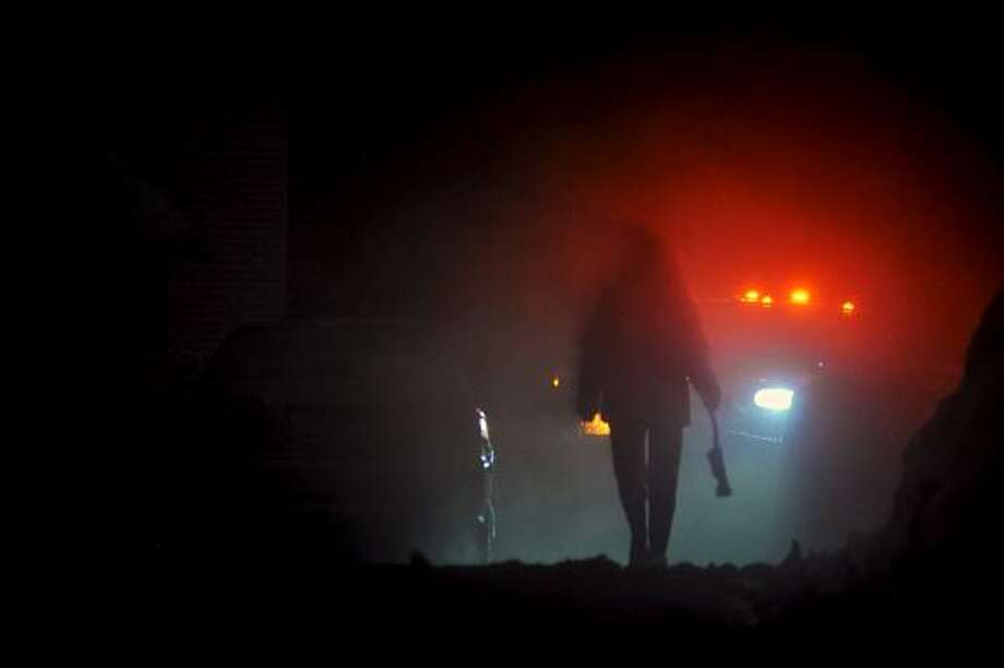 Catherine Avalone/The Middletown PressA woman walks with a snow brush in Middletown Monday evening. / TheMiddletownPress