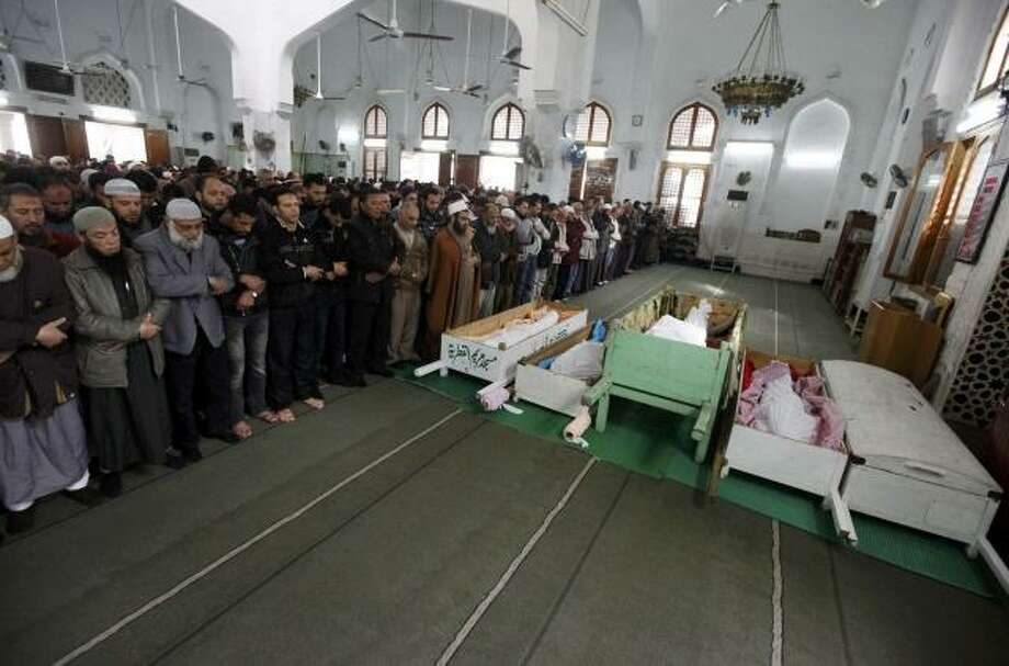 Mourners pray next to the bodies of victims of Wednesday's soccer violence at Port Said stadium during their funeral in Port Said Thursday. Seventy-four people were killed when supporters clashed at an Egyptian soccer match, prompting fans and politicians on Thursday to turn on the ruling army for failing to prevent the deadliest incident since Hosni Mubarak was ousted. (Reuters/Mohamed Abd El-Ghany) Photo: REUTERS / X02738