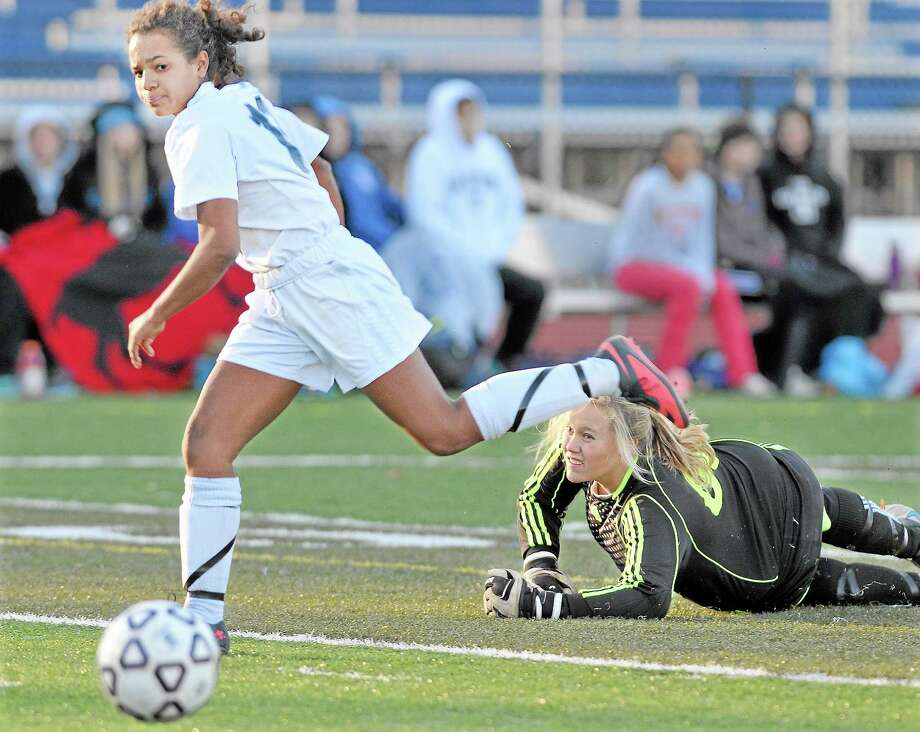 Middletown sophomore Samantha Fletcher challenges Hall goalie Madison Hooper and scores the second goal giving the Blue Dragons a 2-1 lead at half-time at Rosek-Skubel Stadium at MHS. The Blue Dragons scored in the final seconds of the game and chalked up a 3-2 win against the Warriors from West Hartford and advances to the CCC semi-finals on Monday. Photo: Photos By Catherine Avalone — The Middletown Press  / TheMiddletownPress