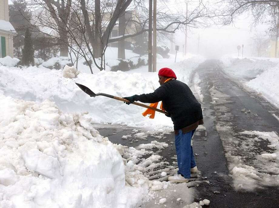 New Haven--Willie Mae Samuel shovels her driveway in Upper Westville as the rain fell causing foggy conditions . Photo-Peter Casolino 2/11/13