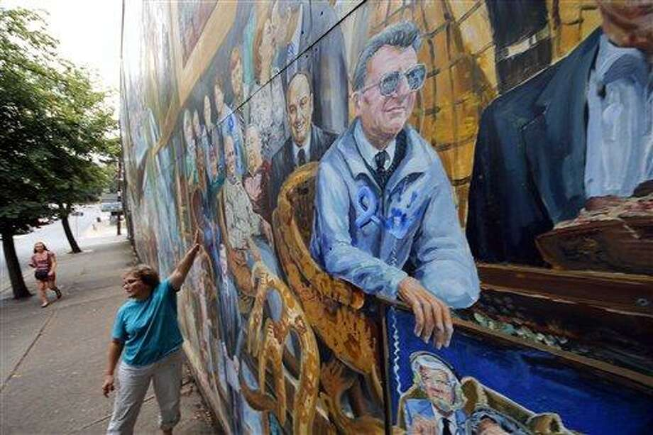A woman touches a mural in downtown State College, Pa., featuring former Penn State head football coach Joe Paterno, center, on Monday, July 23, 2012. Penn State football was all but leveled Monday by an NCAA ruling that wiped away 14 years of coach Joe Paterno's victories and imposed a mountain of fines and penalties, crippling a program whose pedophile assistant coach spent uncounted years molesting children, sometimes on university property. (AP Photo/Gene J. Puskar) Photo: AP / AP