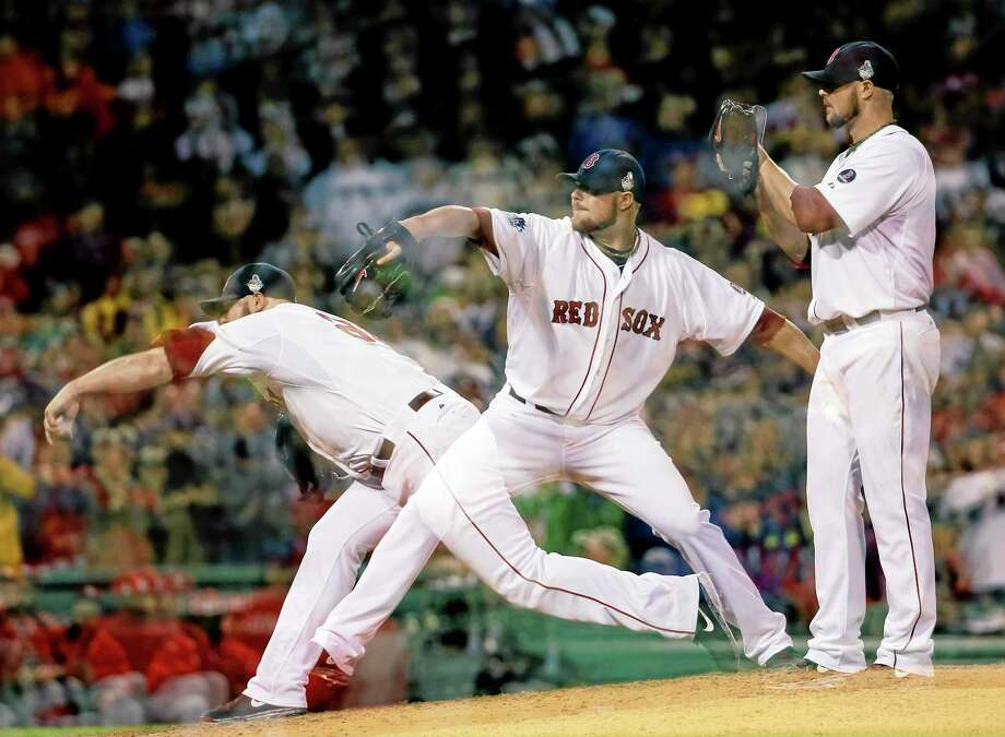 This multiple exposure image shows Red Sox starting pitcher Jon Lester throwing during the seventh inning of Game 1 of the World Series against the St. Louis Cardinals Wednesday at Fenway Park in Boston. Photo: David J. Phillip — The Associated Press  / AP