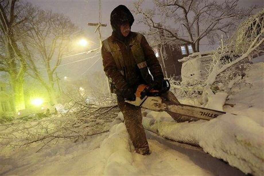 Louie Rodriguez of the New Bedford Forestry Department cuts a fallen tree at the intersection of Rotch St. and Maple St. in New Bedford, Mass., on Friday, Feb. 8, 2013, after heavy snow and winds from a storm. Snow began falling across the Northeast on Friday, ushering in what was predicted to be a huge, possibly historic blizzard and sending residents scurrying to stock up on food and gas up their cars. The storm could dump 1 to 3 feet of snow from New York City to Boston and beyond. (AP Photo/Standard Times, Peter Pereira) Photo: AP / Standard Times