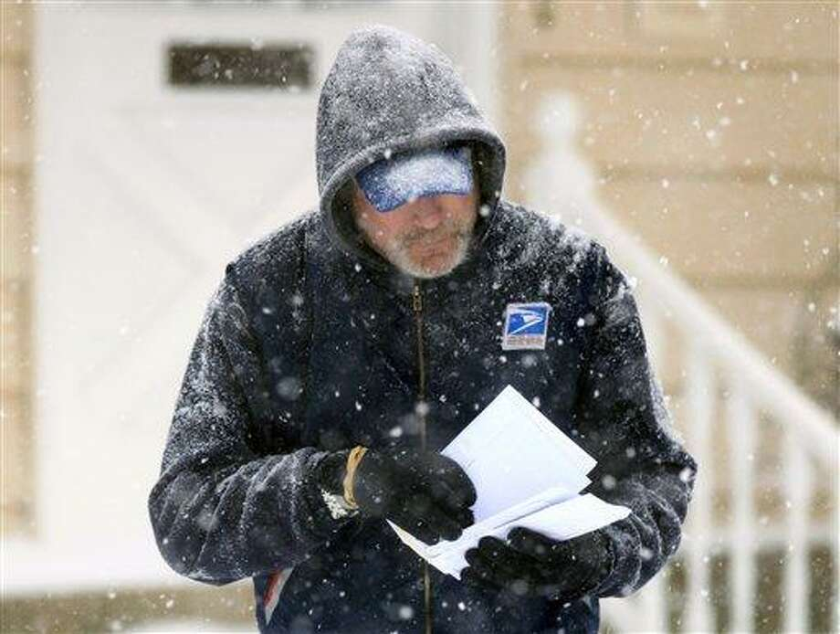 In this Saturday Dec. 19, 2009 file photo, U. S. Post Office letter carrier Tim Bell delivers the mail during a snow storm in Havertown, Pa.  The financially struggling U.S. Postal Service says it will stop delivering mail on Saturdays but continue to deliver packages six days a week under a plan aimed at saving about $2 billion a year. In an announcement scheduled for later Wednesday Feb. 6, 2013, the service is expected to say the Saturday mail cutback would begin in August.  (AP Photo/Jacqueline Larma) Photo: AP / AP