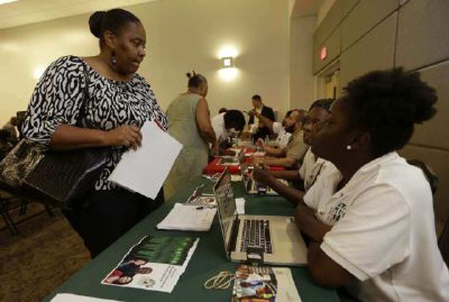 In this Oct. 3, 2013 photo, Velicia Martin, 53, of Miami, left, talks with employees with the Jesse Trice Community Center about insurance options under the Affordable Care Act. Due to technology problems with a federal government website, many were unable to enroll online for the first few days of the program.