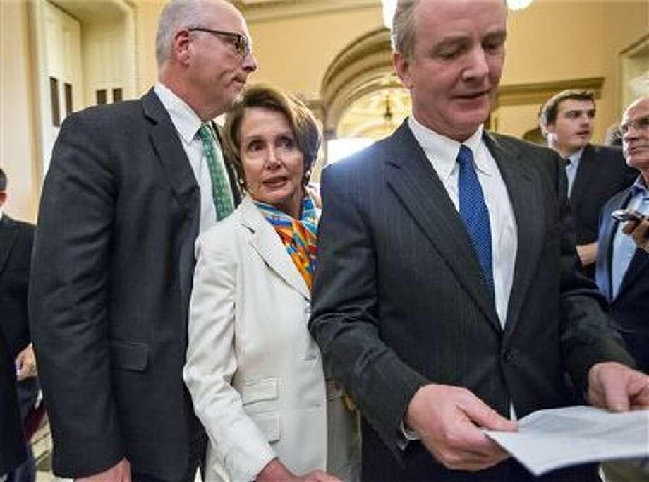 House Minority Leader Nancy Pelosi, D-Calif., center, squeezes between Rep. Joe Crowley, D-N.Y., left, and Rep. Chris Van Hollen, D-Md., right, as they return to negotiations Sept. 30. Photo: AP / AP