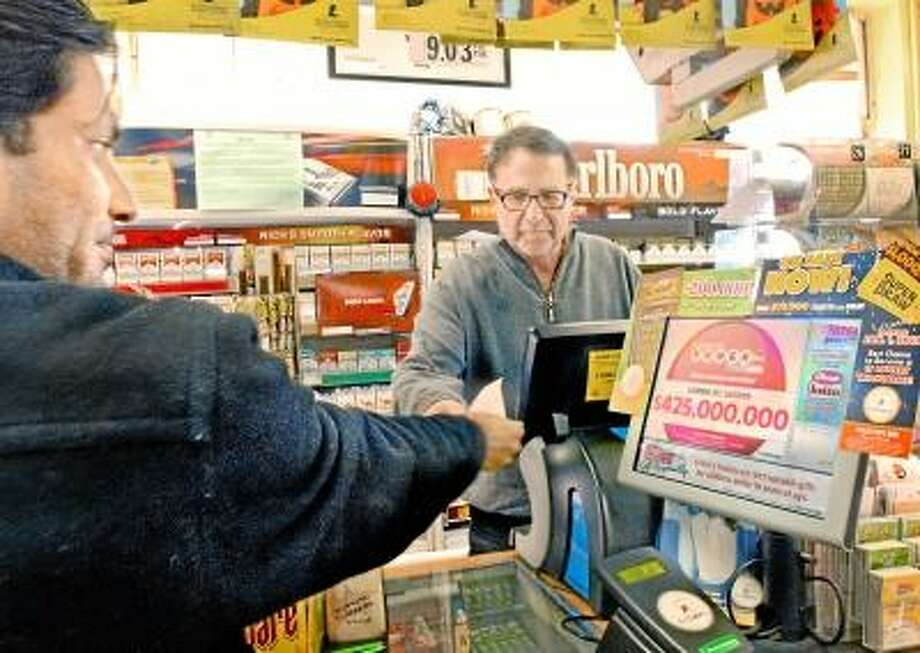 New Haven-Dakshesh Patel. of New Haven, buys powerball tickets from Gerry Katz, owner of Gerry's Shell Food Mart. The powerball jackpot has reached $425,000,000.     Melanie Stengel/Register