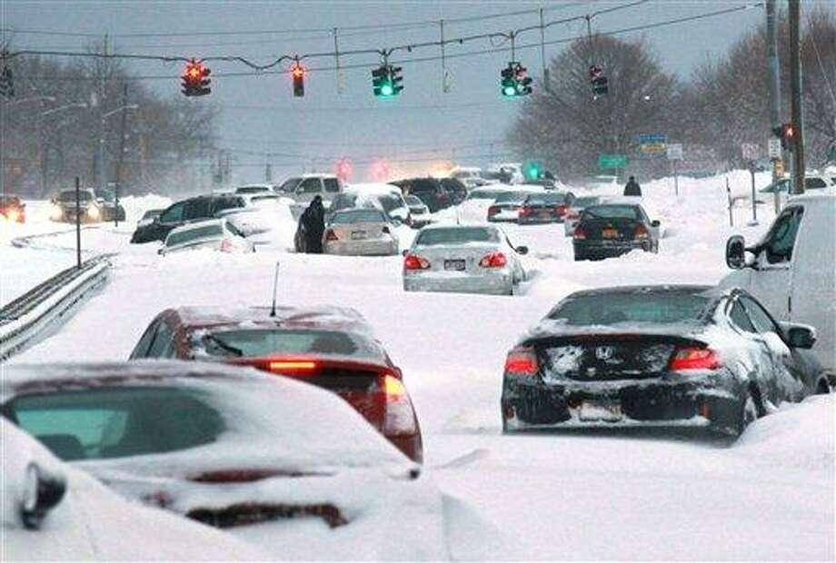 Snowbound vehicles remain stranded Saturday morning, Feb. 9, 2013 along Route 347 in Lake Grove, N.Y. Hundreds of cars were stranded on New York's Long Island roadways as snow rapidly covered roadways. Many people abandoned their vehicles and first responders rescued motorists who chose to spend the frigid night in their vehicles.  (AP Photo/Newsday, John Paraskevas) Photo: AP / Newsday