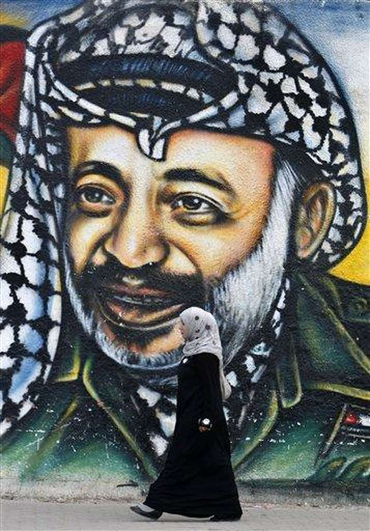 A Palestinian woman walks past a mural of late Palestinian leader Yasser Arafat, in Gaza City, Tuesday, Nov. 27, 2012. Palestinian authorities on Tuesday opened Yasser Arafat's grave and foreign experts took samples from his remains as part of a long-shot attempt, eight years after the iconic leader's mysterious death, to determine whether he was poisoned, as relatives and some political successors have claimed. (AP Photo/Adel Hana)