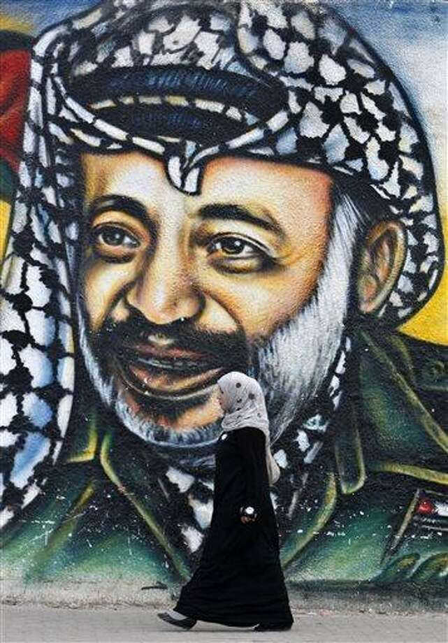 A Palestinian woman walks past a mural of late Palestinian leader Yasser Arafat, in Gaza City, Tuesday, Nov. 27, 2012. Palestinian authorities on Tuesday opened Yasser Arafat's grave and foreign experts took samples from his remains as part of a long-shot attempt, eight years after the iconic leader's mysterious death, to determine whether he was poisoned, as relatives and some political successors have claimed.  (AP Photo/Adel Hana) Photo: AP / AP