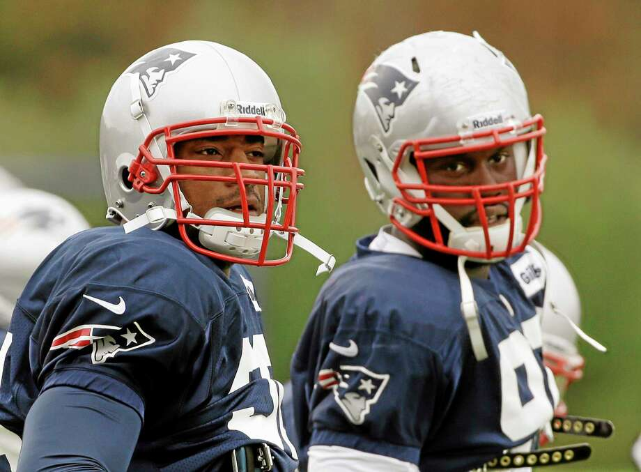 New England Patriots defensive end Chandler Jones, right, and defensive end Andre Carter stand next to each other during a stretching and drills session before practice at the team's facility Wednesday in Foxborough, Mass. The Patriots re-signed Carter on Wednesday and will play the Miami Dolphins Sunday. Photo: Stephan Savoia — The Associated Press  / AP