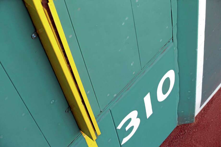Baseball scuff marks are seen on the Green Monster at Fenway Park in Boston. Up close, the famous left-field wall is pocked with thousands of dents and white scuff marks left from decades of doubles that banged off of its facade. Some of the spots are so well-defined that you can even make out the red stitches from the baseball, the Rawlings logo or the Major League Baseball insignia left behind on the green background. Photo: Elise Amendola — The Associated Press  / AP