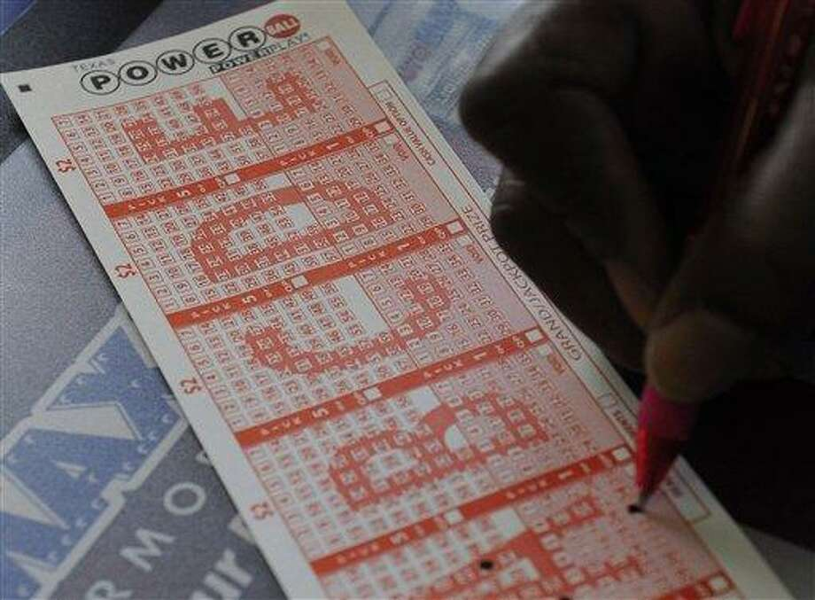 A customer fills in his numbers on a Powerball ticket Monday in Houston for a chance to win. Associated Press Photo: AP / AP