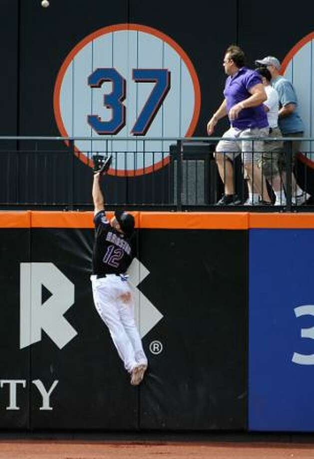ASSOCIATED PRESS New York Mets left fielder Scott Hairston (12) leaps into the air to try to catch a two-run home run hit by Los Angeles Dodgers' Juan Uribe in the ninth inning of Saturday's game at Citi Field in New York. The Dodgers won 8-5.