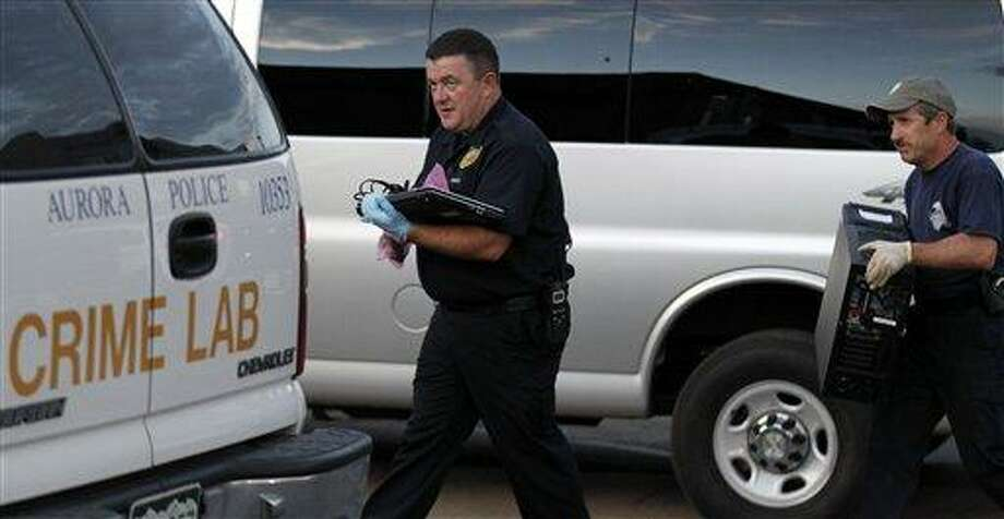 "Investigators remove computer equipment as evidence from the apartment of alleged gunman James Holmes, Saturday, July 21, 2012 in Aurora, Colo. Authorities reported that 12 died and more than three dozen people were shot during an assault at a movie theatre midnight premiere of ""The Dark Knight Rises."" (AP Photo/Alex Brandon) Photo: AP / AP"