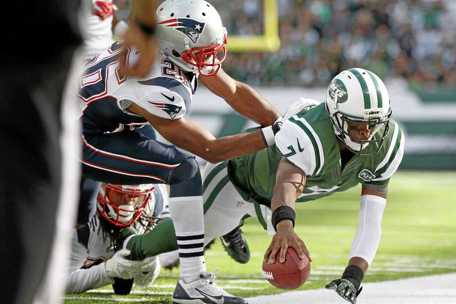 New York Jets quarterback Geno Smith dives out of bounds during the second half of Sunday's game against the New England Patriots. Photo: Kathy Willens — The Associated Press  / AP