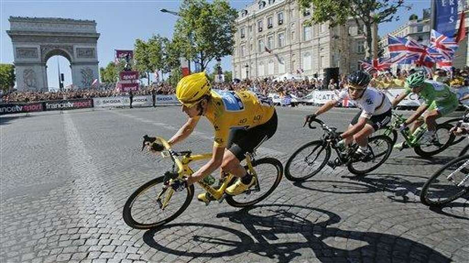 Bradley Wiggins of Britain, wearing the overall leader's yellow jersey is followed by teammate Mark Cavendish of Britain and Peter Sagan of Slovakia, wearing the best sprinter's green jersey as they pass the Arc de Triomphe during the 20th stage of the the Tour de France cycling race over 74.6 miles with start in Rambouillet and finish in Paris, France, Sunday. Associated Press Photo: AP / AP