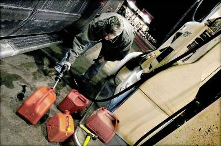 Catherine Avalone/The Middletown Press Middletown resident David Stafford fills a total of six gas tanks in preparation of the blizzard early Thursday evening at the Irving Gas Station Irving at 543 Washington Street in Middletown. / TheMiddletownPress