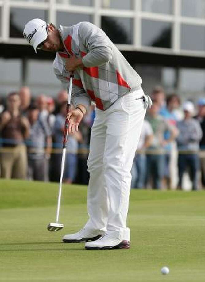 ASSOCIATED PRESS Adam Scott of Australia putts on the 16th green at Royal Lytham & St Annes golf club during the third round of the British Open Golf Championship, Lytham St Annes, England, on Saturday. Scott leads Graeme McDowell by four shots entering the final round. Scott is looking to win his first major.