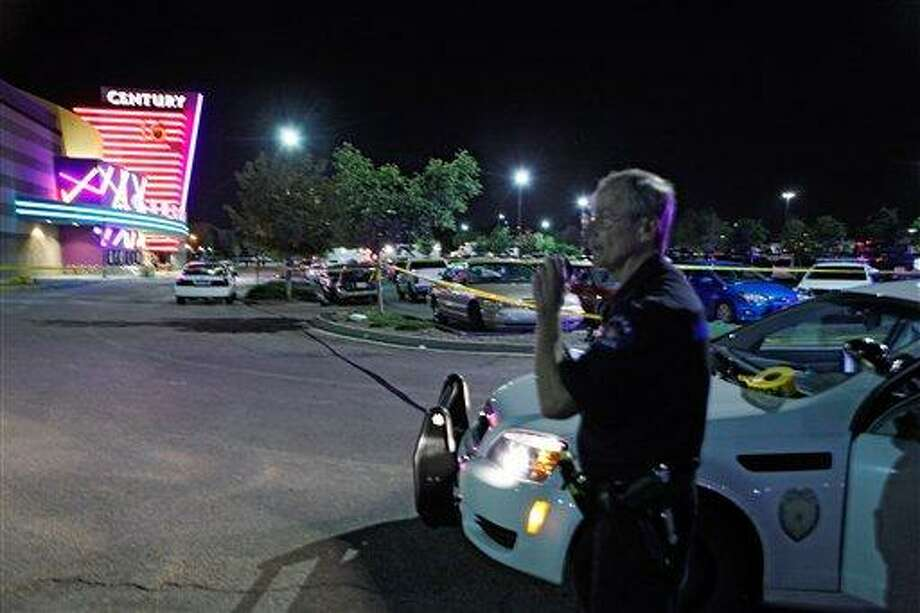 An Aurora Police officer talks on his radio outside of the Century 16 theater at Aurora Mall where as many as 14 people were killed and many injured at a shooting at the Century 16 movie theatre in Aurora, Colo., Friday, July 20, 2012. (AP Photo/Ed Andrieski) Photo: AP / AP