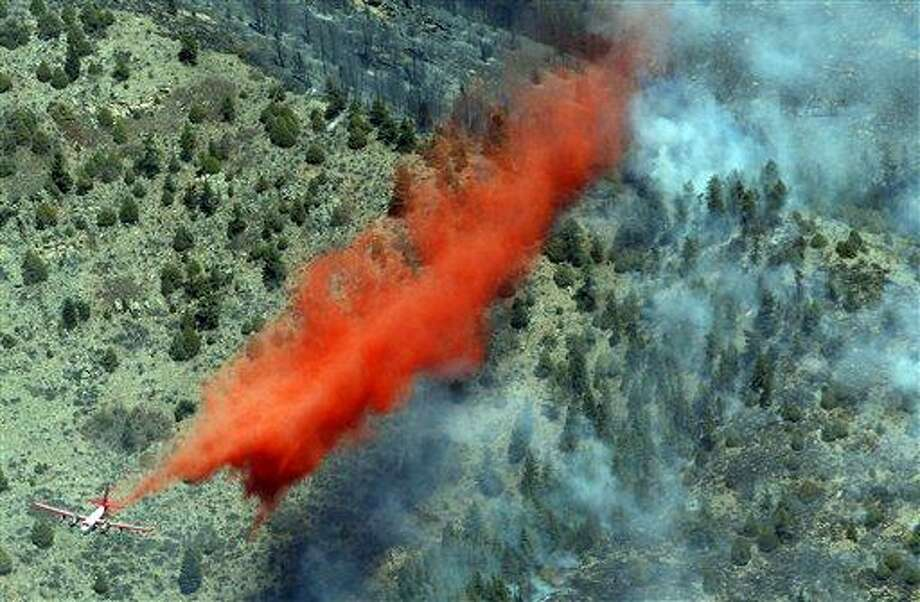 A trail of slurry is deposited by a bomber during a run over a smoldering ridge in the Lower North Fork Wildfire burning in the foothills community of Conifer, Colo., southwest of Denver on Tuesday. Firefighters are now able to actively battle the blaze on the ground that started on Monday and has already destroyed at least 16 homes in the rugged terrain. Associated Press Photo: ASSOCIATED PRESS / AP2012
