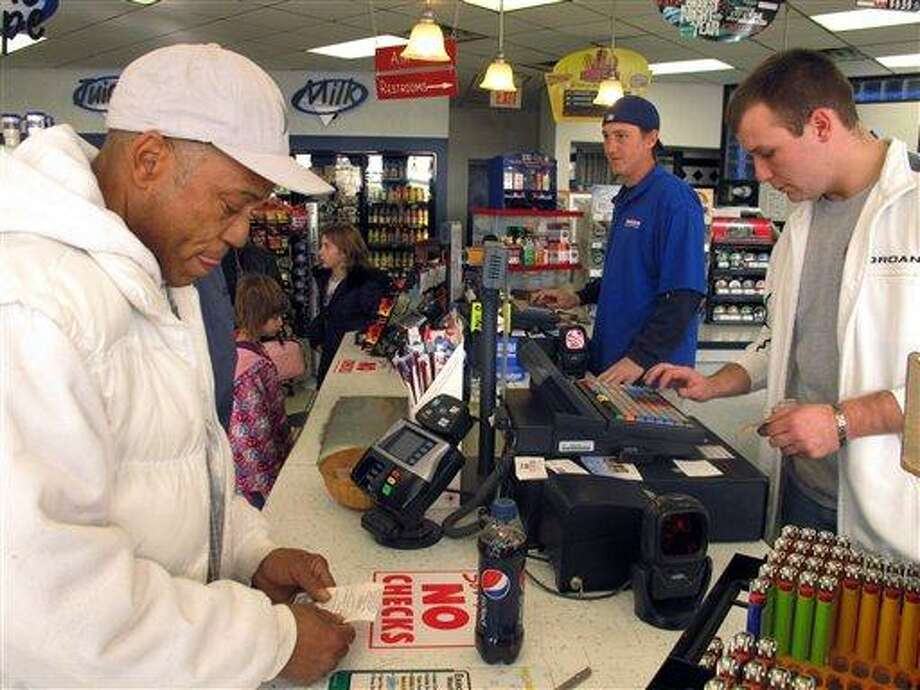 Michael Arrington, left, buys a Powerball ticket from cashier Lee Heilig, right, on Friday, Nov. 23, 2012, at a DeliMart convenience store in Iowa City, Iowa. AP Photo/Grant Schulte Photo: AP / AP