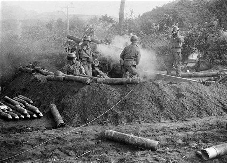 In this 1950 back-and-white file photo, American GIs fire a 105 Howitzer gun in action against North Korean invaders somewhere in Korea. The U.S. said Wednesday it is suspending efforts to recover remains of thousands of fallen service members in North Korea, the latest sign that a recent thaw in diplomatic relations is over. The U.S. was in the process of resuming the hunt for remains missing from the 1950-53 Korean War. Associated Press Photo: AP / AP