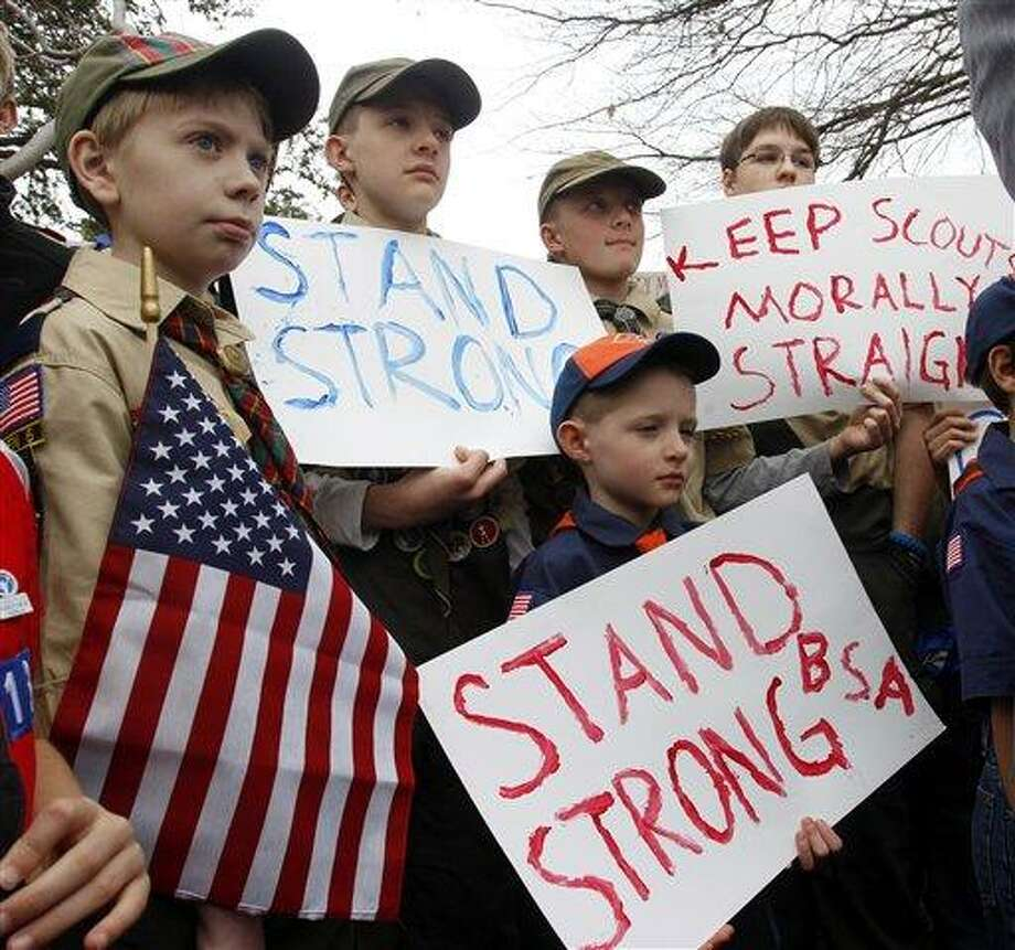 "Clockwise from left, Boy Scouts Eric Kusterer, Jacob Sorah, James Sorah, Micah Brownlee and Cub Scout John Sorah hold signs at the ""Save Our Scouts"" Prayer Vigil and Rally in front of the Boy Scouts of America National Headquarters in Irving, Texas, Wednesday, February 6, 2013.  The Boy Scouts of America said Wednesday it needed more time before deciding whether to move away from its divisive policy of excluding gays as scouts or adult leaders.  (AP Photo/Richard Rodriguez) Photo: AP / FR170526 AP"