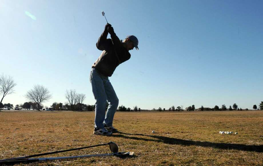 Chris Bogucki of Clinton is a docent at the Meigs Point Nature Center at Hammonasset Beach State Park in Madison, so he can often stop at the campgrounds to practice his golf swing in the mild winter weather. Mara Lavitt/Register 2/3/12