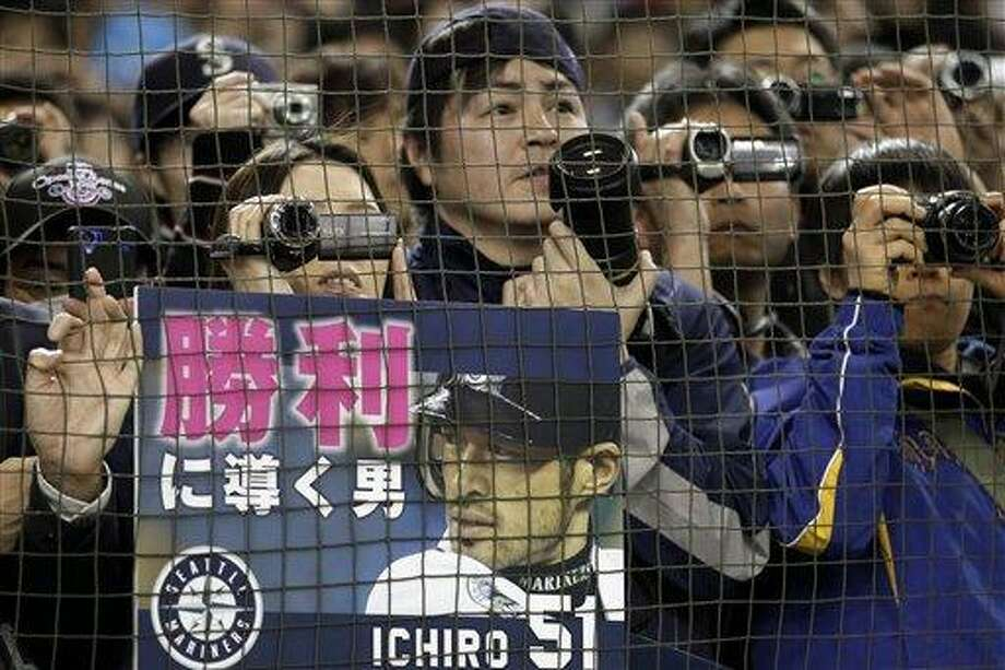 "Fans with a placard cheering Seattle Mariners outfielder Ichiro Suzuki watch the team's batting practice prior to the American League season opening MLB baseball game between the Oakland Athletics and the Mariners at Tokyo Dome in Tokyo, Wednesday, March 28, 2012. The placard reads: ""The man who leads to victory."" (AP Photo/Shizuo Kambayashi) Photo: AP / AP"