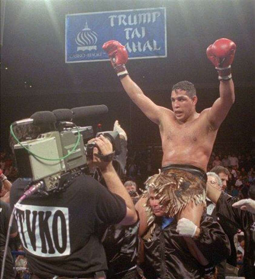 "FILE - This June 22, 1996, file photo shows Hector ""Macho"" Camacho being lifted into the air after his unanimous decision over Roberto Duran in an IBC middleweight title fight at the Trump Taj Mahal Casino Resort in Atlantic City, N.J. Police in the Puerto Rican city of Bayamon say they found drugs inside the car in which former champion boxer Camacho was shot and critically wounded. Camacho was in critical condition Wednesday, Nov. 21, 2012, at the Centro Medico trauma center in San Juan. (AP Photo/Donna Connor, File) Photo: ASSOCIATED PRESS / A1996"