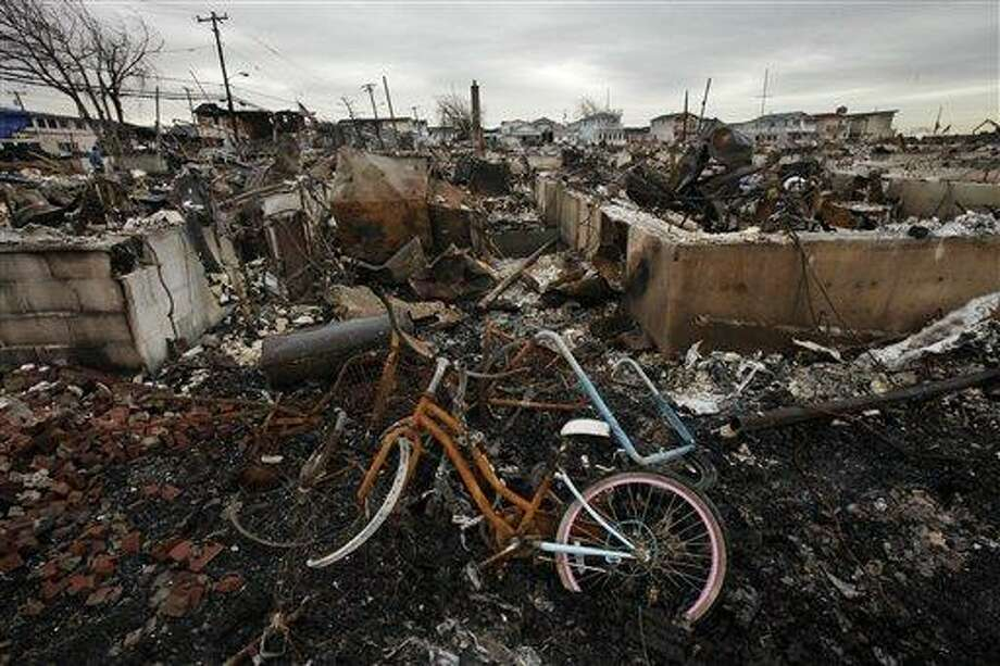 FILE - In this Nov. 13, 2012 file photo, a burned bicycle lies in the ashes of a burned out home in the Breezy Point section of the Queens borough of New York. More than 50 homes were lost in a fire that swept through the oceanside community during Superstorm Sandy. Some residents of New York City's storm-battered Breezy Point neighborhood say thieves looted their damaged houses over Thanksgiving. (AP Photo/Mark Lennihan, File) Photo: AP / AP