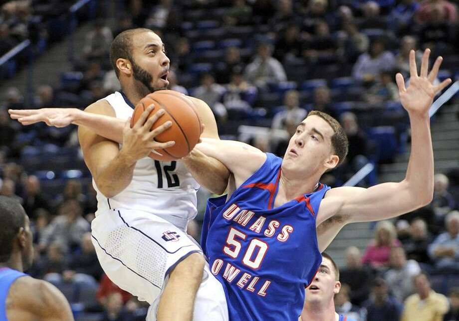 Connecticut's R.J. Evans, left, is fouled by Massachusetts Lowell's James McDonnell during the first half of an exhibition college basketball game in Hartford, Conn., Sunday, Nov. 4, 2012. (AP Photo/Fred Beckham) Photo: AP / AP2012
