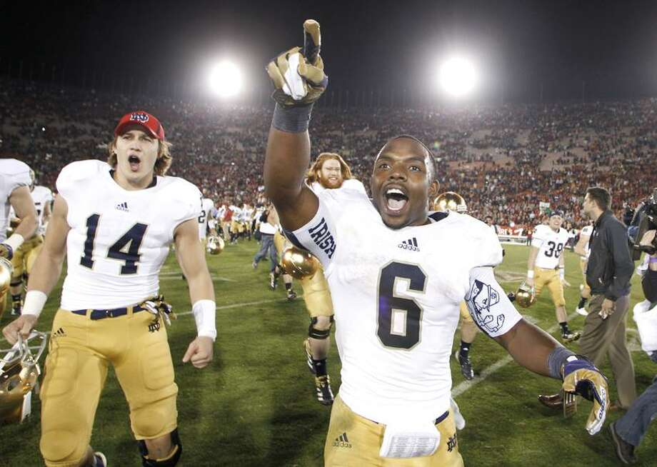 Notre Dame running back Theo Riddick, right, and wide receiver Luke Massa, left, celebrate after Notre Dame defeated Southern California 22-13 in an NCAA college football game, Saturday, Nov. 24, 2012, in Los Angeles. (AP Photo/Danny Moloshok) Photo: AP / AP2012