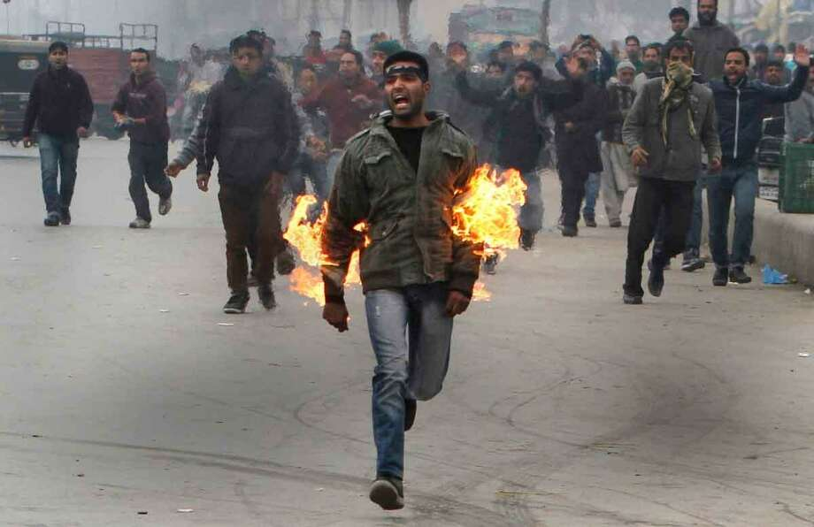 A Kashmiri Shiite mourner runs after he set himself on fire during a Muharram procession in Srinagar, India, Friday, Nov. 23, 2012. The Kashmiri man was protesting a police ban on religious processions marking the Muslim month of Muharram in Indian-controlled Kashmir's main city. Police said that clashes erupted when troops tried to stop groups of Shiite Muslims from gathering. (AP Photo) Photo: ASSOCIATED PRESS / AP2012